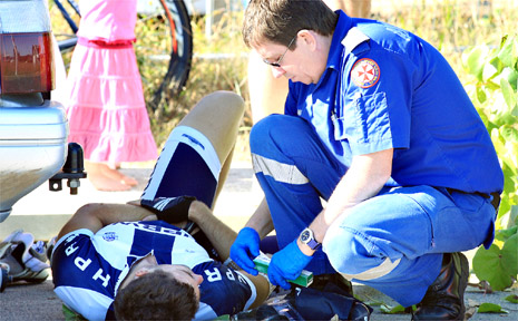 A NSW Ambulance officer attends to a fallen cyclist at the Battle of the Border cycling event.