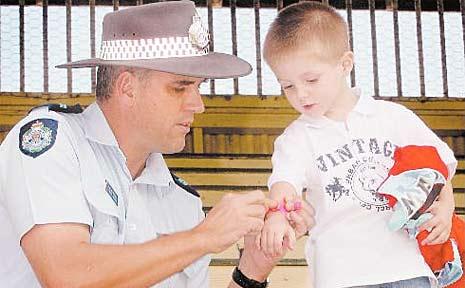 Sergeant Nigel Dalton places an identification wristband on Alex Martin.