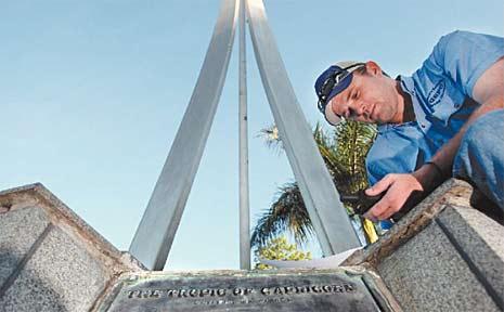 Surveyor's assistant Shaun Reed, of Rockhampton, carefully checks the GPS co-ordinates at the Capricorn Spire.