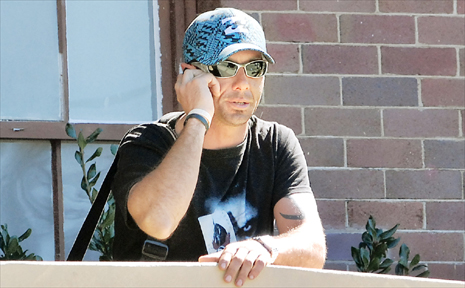 Bradley Harris chats on his mobile phone after his court case yesterday