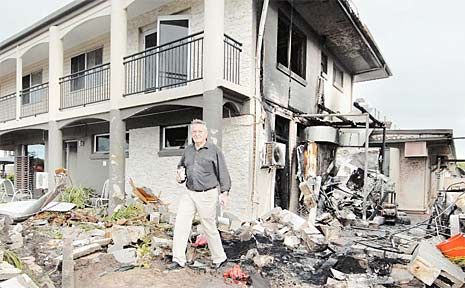 Country Plaza Motor Inn part-owner Keith Ryan inspects the fire damage outside his motel after a truck crossed into the path of oncoming traffic and ploughed into gas cylinders.