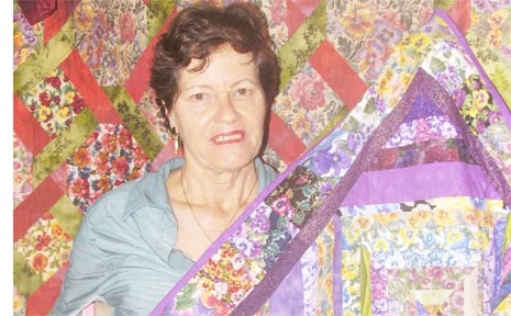 Liz Watts and two of her patchwork quilts.