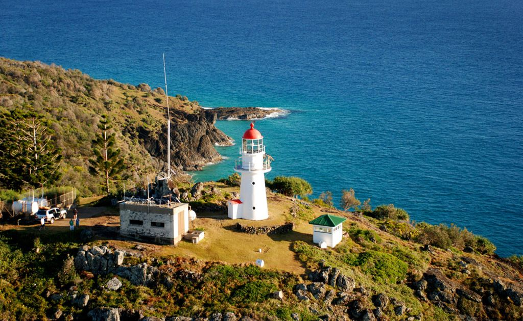 The Double Island Point Light house sits atop the rocky cliff looking over the Coral Sea.