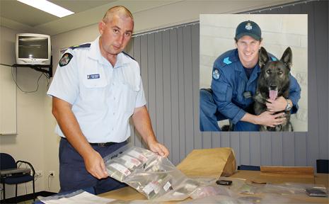 Senior Sergeant Mick Searle examines marijuana seized in a drug raid.