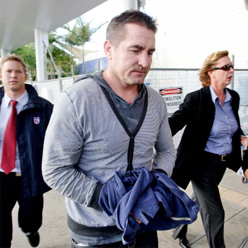 Former Sydney Swans AFL star Daryn Cresswell used a jumper to cover his handcuffs as he arrived at the Sunshine Coast Airport. Photo: Cade Mooney/183658