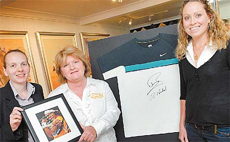 On Q Events organiser Brooke Qualischefski, left, and Skye Gregory, right, show CQ Rescue's Leonie Hansen the signed T-shirt work by Nadal in the Australian Open.