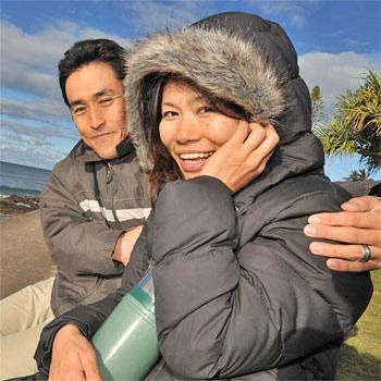 Local Maroochydore residents Naoto and Chizuko Arakawa try and stay warm. Photo:John McCutcheon/183778