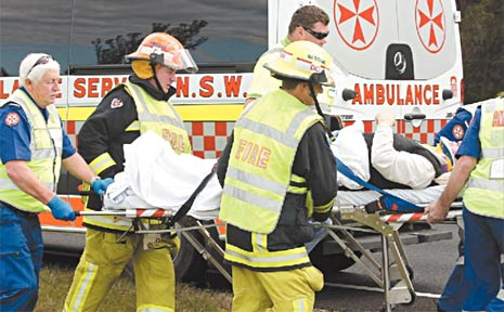 Rescuers tend to the man whose car flipped on its roof on the Pacific Highway at Chinderah.
