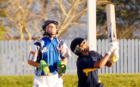 Delhi batsman Chander Thappa hits high as Mackay Whitsunday's Kellen Powell looks on.