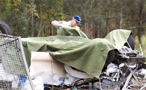 Police place a tarpaulin over the upturned car until the Ballina crash investigation unit arrived.