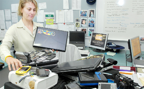 Detective Senior Constable Alisha Keogh looks through the mountain of stolen property seized by Mackay police last week.