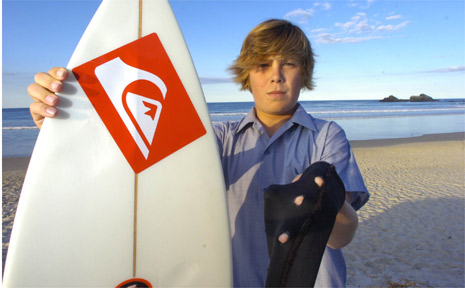 Zac Skyring shows off the holes in his wetsuit after a shark knocked him off his surfboard at Broken Head last week.