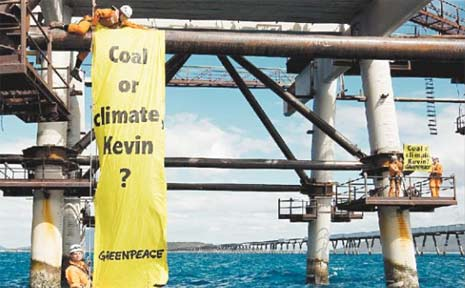 Four Greenpeace activists spent last night behind bars in Bowen after they climbed from an inflatable boat and locked themselves to part of the Abbot Point Coal Terminal.