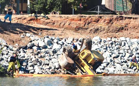 FIREFIGHTERS set up a hydrocarbon boom to ensure any soil spilt from an excavator which tooppled in the river is contained.