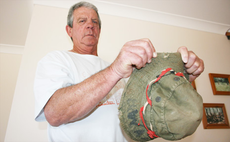 Warren Pearson shows the shrapnel holes in the bush hat he was wearing the day he stepped on a booby trap in Vietnam in 1966.