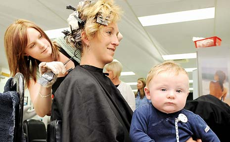 STYLISH: Student hairdresser Hayley Smith from Hair Chic at Evans Head works on hair model Penny Dehoon, of Goonellabah, with her six-month-old son Isaac Graham at Wollongbar TAFE.