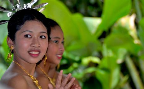 A Thai woman stops to wave sawadee ka (hello) during a traditional dance.