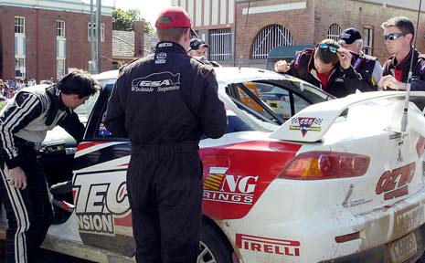 DAMAGE: Pit crew members look at the damage caused by a rock thrown through the back windscreen of the rally car driven by Steven Shepheard and co-driver John McCarthy.