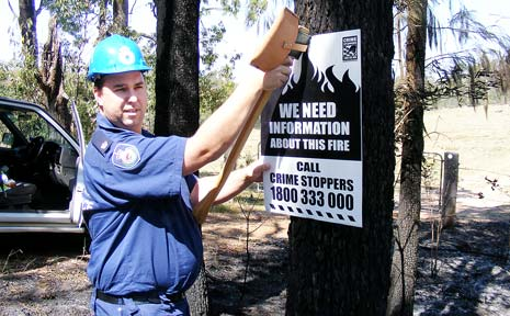 BUG HUNT: Rural Fire Service investigator, Inspector Daniel Ainsworth puts up a notice seeking help to catch a suspected arsonist in theDyraaba area.