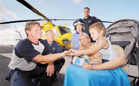Jake Bryan, 3, gives RACQ-CQ Rescue pilot Brendon Barron a high five. Behind, from left, is air crewman Mark Donovan, Jake's big brother Paul, paramedic Dan Basham and Jake's mum Karina Bryan.