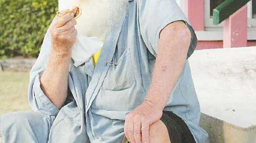 John Guest sits outside a Rockhampton business with his meat pie and bottle of milk.