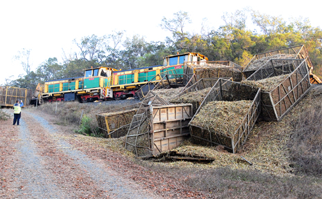 Full cane train bins on their way to Farleigh Mill were yesterday strewn down the side of an overpass after two locomotives had a head-on collision near Habana.