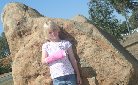 BETWEEN A ROCK AND A HARD PLACE: Eight-year-old Biloela girl Caiti Popple fell off this rock at Lions Park and broke her wrist last week. Her parents want signs and a soft fall area installed.