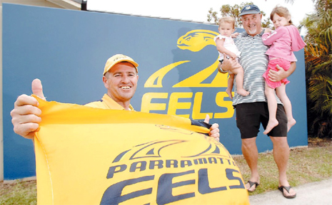 SO CLOSE: Lifetime Eels fans Wayne Keys of Ballina (front) and Tom Connor with his grand-daughters Rubi-Jean, 1, and Paige, 4, in front of the wall he had painted in support of his favourite team.