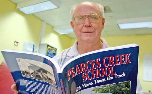 Ian Kirkland with a copy of his book, celebrating 125 years at Pearces Creek School.