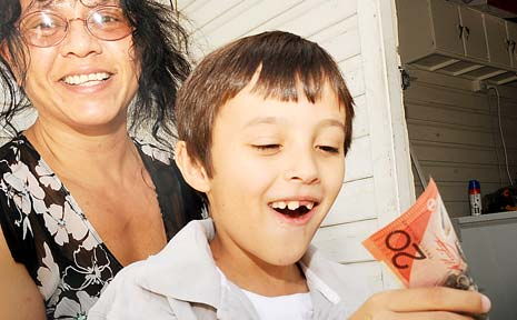 IT'S SAFE: Fiona Rutherford watches son Kyle, 8, put some birthday money into his piggy bank.