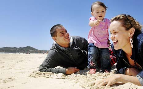 LUCKY ONES: Byron Bay locals Aaron and Kylie Milek-Zaini, with daughterNirmali, enjoy a windy but sunny day on Main Beach.