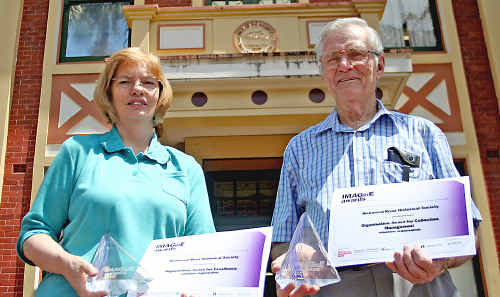 Museum volunteer Kerrie Alexander and Geoff Foley with the awards outside the Richmond River Historical Society Museum in Lismore.