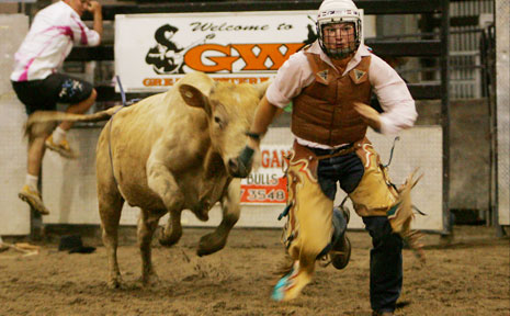 "Justin Carena tries to outrun the bull Ultimate Warrior after the pair parted company during the Rookie Bull Ride at the Bulls and Barrels ""Tough Enough to Wear Pink"" Girls Grammar Rodeo at the Great Western on Saturday night."