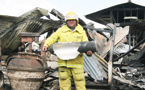 BLOWN APART: Baralaba fire brigade captain Rob Price with the remians of a gas cylinder that exploded during TUesday's fire.