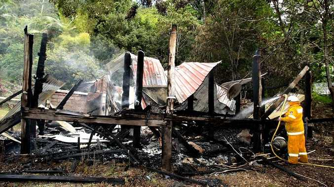 A firefighter works to contain a house fire on Mt Warning Road.