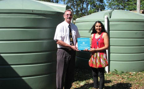 School principal Tim Edwards and school parent and grant driver Bev Dhnaram are pictured with the two water tanks.