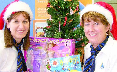 Bank of Queensland employees Michelle Barrett and Dani Siddans get ready to stock up on gifts for disadvantaged children.