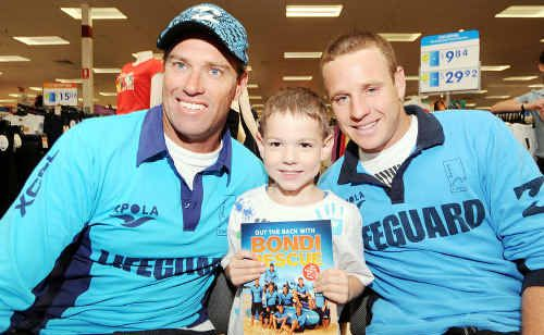 Young fan Cooper Semmens, 5, gets an autograph from Hoppo, left, and Whippet at the launch of the Bondi Rescue book at Kawana Shoppingworld yesterday.