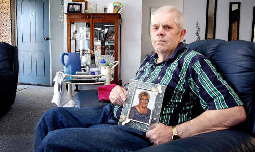 A file photo of Robert Davison with a photo of his wife Carol, who died in the two-car collision.