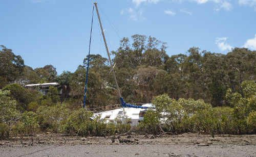 A yacht stranded in mangroves at River Heads has been there for almost a year.