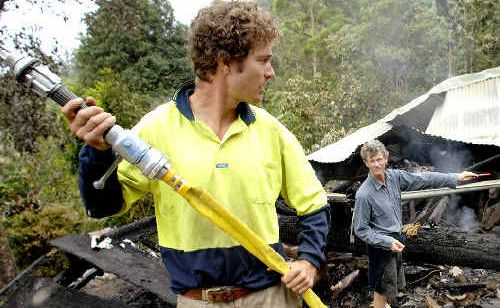 Lynda Mallaby's son, Erin Young (left) and her brother John, extinguish the smouldering debris of her house at The Channon.