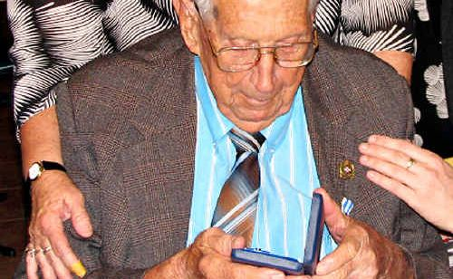 Bill Powell studies his medal, awarded on his 100th birthday.