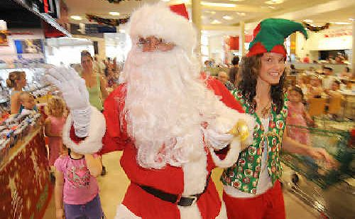 Santa arrives at Hinkler Central Shopping Centre with his little helper Elizabeth Hansen on Saturday.
