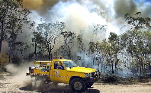 A Nikenbah rural fire truck skirts around the blaze at Takura that burnt about 150 hectares after starting alongside Torbanlea-Pialba Road.