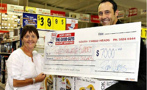 GOOD Guys Tweed Heads South proprietor Rory Curtis presents a $7000 cheque to Tweed Palliative Care president Meredith Dennis.