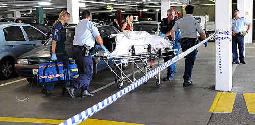 Ambulance officers wheel the stabbing victim to the waiting ambulance.