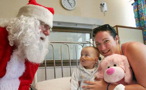Sophie Stephenson with mum Melita Nelson receives a stuffed toy from Santa Claus yesterday at the Rockhampton Hospital's children's ward.