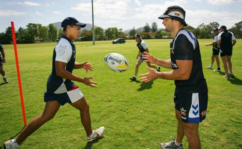 North Queensland Cowboys player Aaron Payne (right) puts Emmaus College student Jordan Saunders through his paces at a training camp on Saturday.
