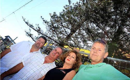Kingscliff builders Gordon Bismire (Green Shirt) and Peter Rigney (white shirt) with owners Bill and Donna Engwirda (Middle), have been ordered to remove Norfolk Pines near a Kingscliff property.