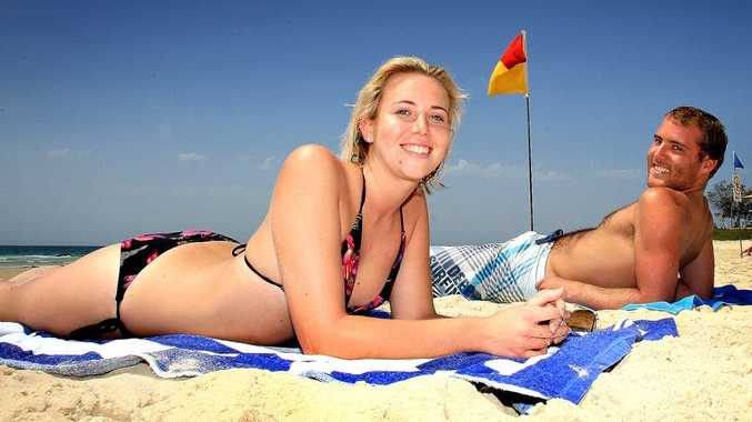 Kirralee Campbell and Lewis Randell at Rainbow Beach yesterday soaking up the sun ahead of summer, which begins today.